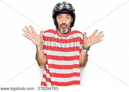 Middle age handsome motorcyclist man wearing moto helmet over isolated white background clueless and confused with open arms, no idea and doubtful face.