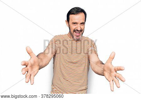 Middle age handsome man wearing striped t-shirt standing over isolated white background looking at the camera smiling with open arms for hug. Cheerful expression embracing happiness.