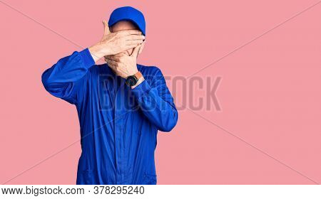 Middle age handsome man wearing mechanic uniform covering eyes and mouth with hands, surprised and shocked. hiding emotion