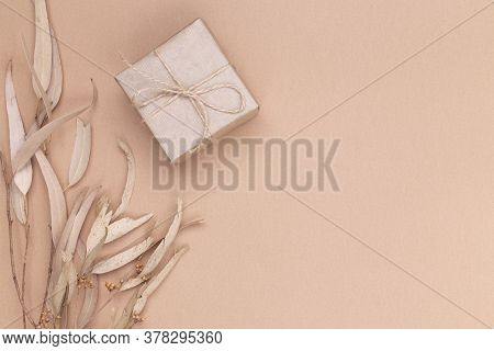 Autumn Composition. Gifts Wrapped In Kraft Paper, Autumn Eucalyptus Leaves, On A Beige Background. F