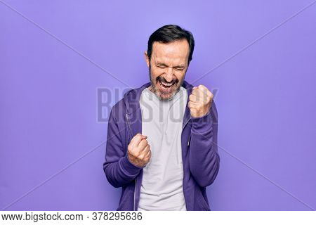 Middle age handsome sporty man wearing casual purple sweatshirt over isolated background celebrating surprised and amazed for success with arms raised and eyes closed