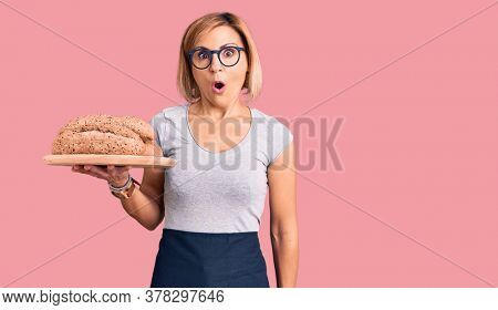 Young blonde woman holding wholemeal bread scared and amazed with open mouth for surprise, disbelief face