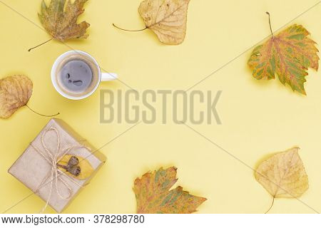 Autumn Composition Frame. Gift Wrapped In Kraft Paper, Autumn Leaves, A Cup Of Coffee On A Yellow Ba