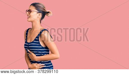 Young beautiful woman wearing casual clothes and glasses with hand on stomach because nausea, painful disease feeling unwell. ache concept.