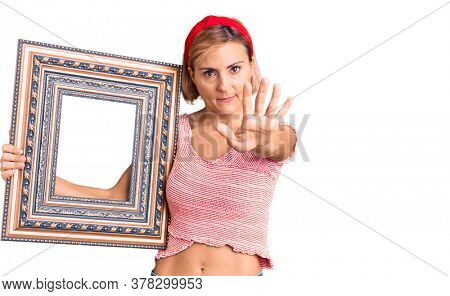Young blonde woman holding empty frame with open hand doing stop sign with serious and confident expression, defense gesture
