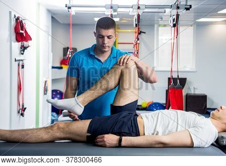 Rehabilitation Therapy. Physiotherapist Working With Young Male Patient