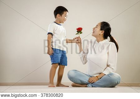 Asian Mother And Child Holding Rose. Vietnamese Boy Gives Parent A Red Rose Flower As A Loving Gestu