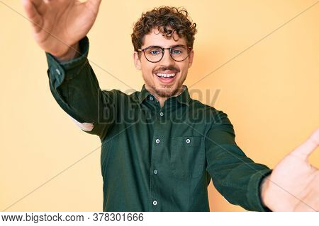 Young caucasian man with curly hair wearing casual clothes and glasses looking at the camera smiling with open arms for hug. cheerful expression embracing happiness.