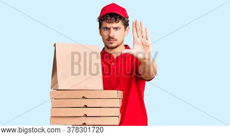 Young handsome man with curly hair holding delivery pizza box with open hand doing stop sign with serious and confident expression, defense gesture