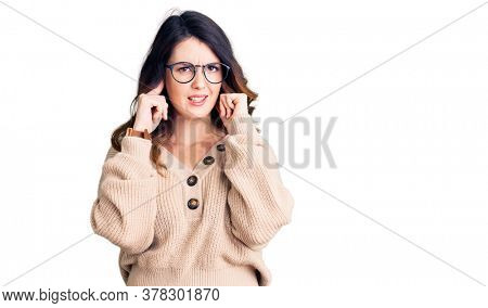 Beautiful young brunette woman wearing casual clothes and glasses covering ears with fingers with annoyed expression for the noise of loud music. deaf concept.
