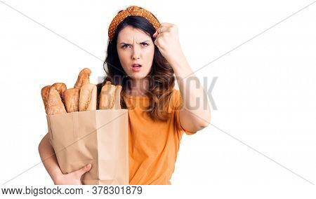 Beautiful young brunette woman holding paper bag with bread annoyed and frustrated shouting with anger, yelling crazy with anger and hand raised