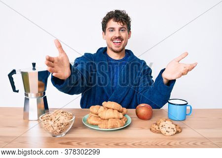 Young caucasian man with curly hair sitting on the table having breakfast looking at the camera smiling with open arms for hug. cheerful expression embracing happiness.