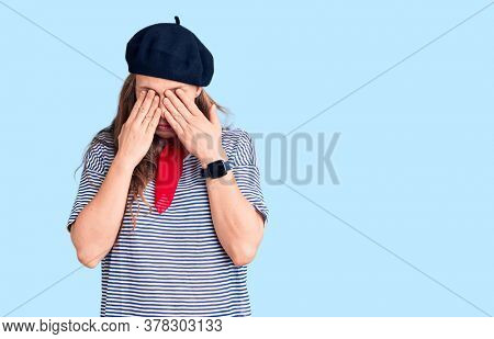 Young beautiful blonde woman wearing french beret and striped t-shirt rubbing eyes for fatigue and headache, sleepy and tired expression. vision problem