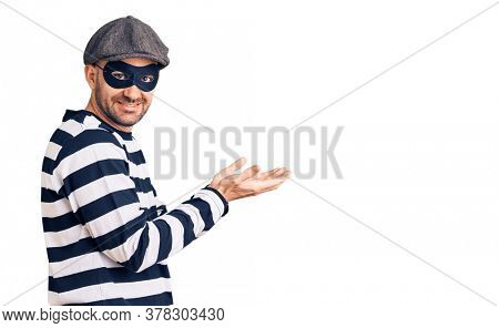 Young handsome man wearing burglar mask pointing aside with hands open palms showing copy space, presenting advertisement smiling excited happy
