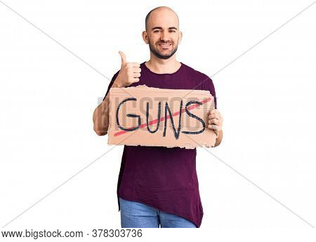 Young handsome man holding prohibited guns banner smiling happy and positive, thumb up doing excellent and approval sign