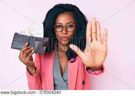 Beautiful african woman holding wallet with dollars with open hand doing stop sign with serious and confident expression, defense gesture