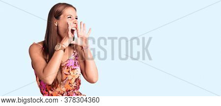 Young beautiful hispanic woman wearing casual clothes shouting angry out loud with hands over mouth