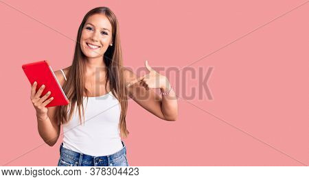 Young beautiful hispanic woman holding touchpad pointing finger to one self smiling happy and proud