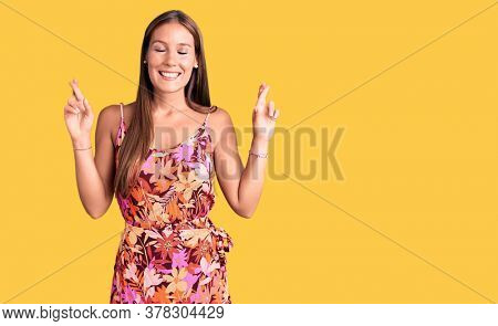 Young beautiful hispanic woman wearing casual clothes gesturing finger crossed smiling with hope and eyes closed. luck and superstitious concept.