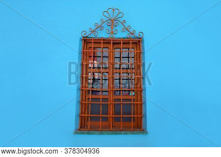 Orange Brown Decorative Wrought Iron Window Isolated On Blue Concrete Wall