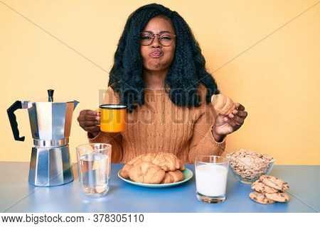 Young african american woman eating breakfast holding croissant puffing cheeks with funny face. mouth inflated with air, catching air.