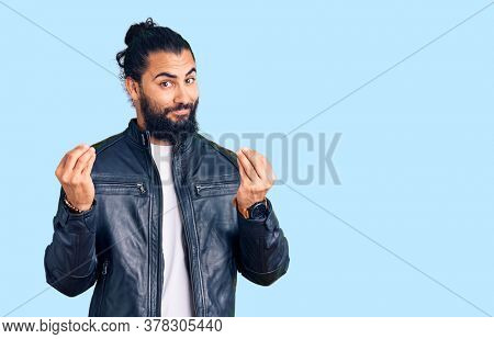 Young arab man wearing casual leather jacket doing money gesture with hands, asking for salary payment, millionaire business