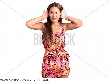 Young beautiful hispanic woman wearing casual clothes trying to hear both hands on ear gesture, curious for gossip. hearing problem, deaf