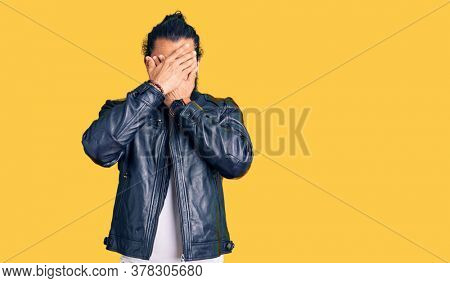 Young arab man wearing casual leather jacket covering eyes and mouth with hands, surprised and shocked. hiding emotion