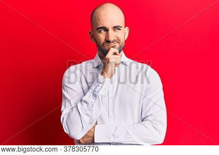 Young handsome bald man wearing elegant shirt thinking concentrated about doubt with finger on chin and looking up wondering