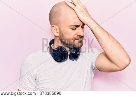 Young handsome bald man listening to music using headphones surprised with hand on head for mistake, remember error. forgot, bad memory concept.