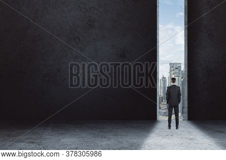 Back View Of Businessman Stands In Doorway And Looking On Modern City In Distance. Success And Chall