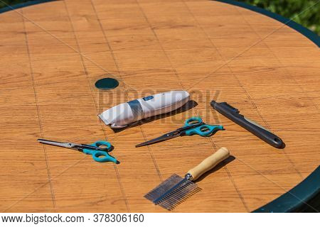 On A Round Brown Plastic Table Is A Set For Cutting Fur And Hair Of Pets. The Set Has Scissors For H