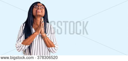 Young african american woman wearing casual clothes and glasses begging and praying with hands together with hope expression on face very emotional and worried. begging.