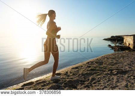 Sportive Lady. Rear View Of Woman Jogging On The Sun Beach In The Daylight, Banner, Copy Space