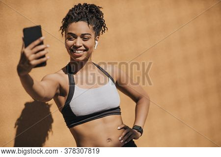 Sports Blog. Smiling African American Young Woman In Sports Bra With Wireless Headphones And Fitness