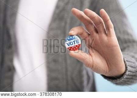 Vote 2020. Law Abiding American Citizen Holding Vote Button In Hand, Blurred Background