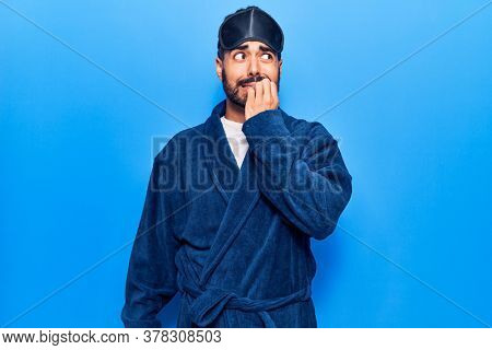 Young hispanic man wearing sleep mask and robe looking stressed and nervous with hands on mouth biting nails. anxiety problem.