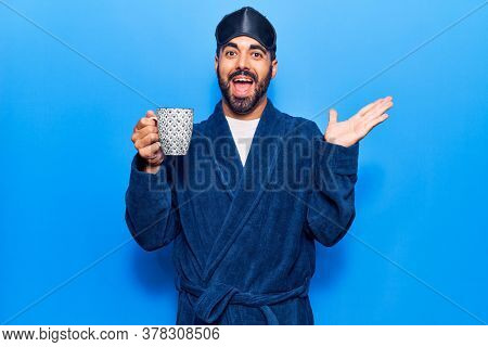 Young hispanic man wearing sleep mask and robe drinking coffee celebrating achievement with happy smile and winner expression with raised hand