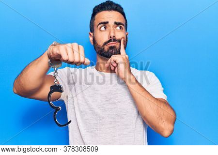 Young hispanic man holding prisoner handcuffs serious face thinking about question with hand on chin, thoughtful about confusing idea