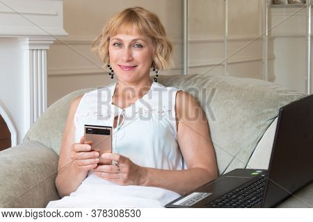 A Beautiful Blonde Woman Of Fifty Looks Good Sits On An Armchair With A Mobile Phone