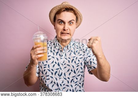 Young handsome redhead man on vacation drinking glass of healthy orange juice annoyed and frustrated shouting with anger, yelling crazy with anger and hand raised