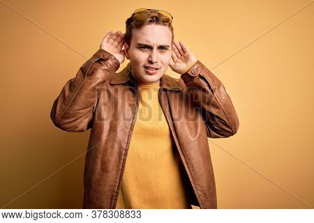 Young handsome redhead man wearing casual leather jacket over isolated yellow background Trying to hear both hands on ear gesture, curious for gossip. Hearing problem, deaf