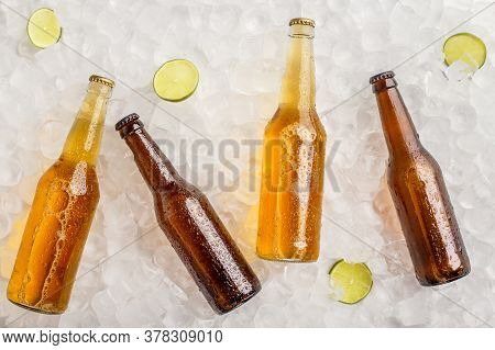 Various Beers Chilled For Party. Cold Glass Bottles With Light And Dark Beer Without Labels In Ice W