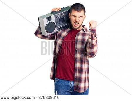 Young handsome man listening to music holding boombox annoyed and frustrated shouting with anger, yelling crazy with anger and hand raised