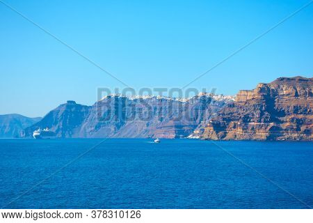 Vew of Aegean Sea with Santorini shore and Fira town on the cliff, Greece