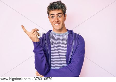 Young handsome man wearing casual purple sweatshirt smiling happy pointing with hand and finger to the side