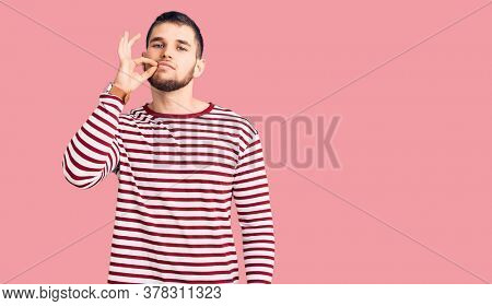 Young handsome man wearing striped sweater mouth and lips shut as zip with fingers. secret and silent, taboo talking