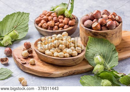 Hazelnuts With Peeled Hazelnut And Leaf  In Brown Bowl On Concrete Background. Hazelnut