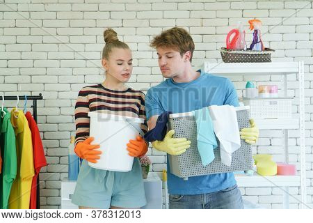 A Young Couple Of Caucasian People Do Chore Together. Attractive Modern Husbands And Wives Smile Hap