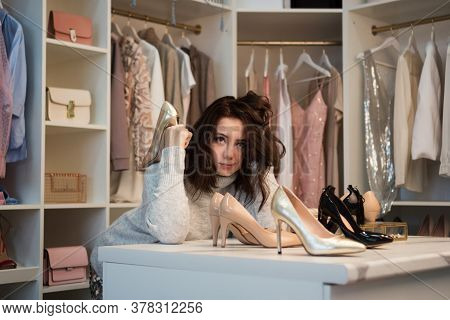 Depressed Woman Standing Near Wardrobe Full Of Clothes, Having Difficult Choice Not Knowing What To